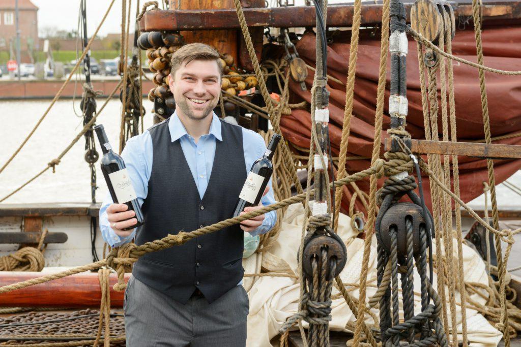 Mann auf Segelschiff hält zwei Flaschen Rotwein in der Hand