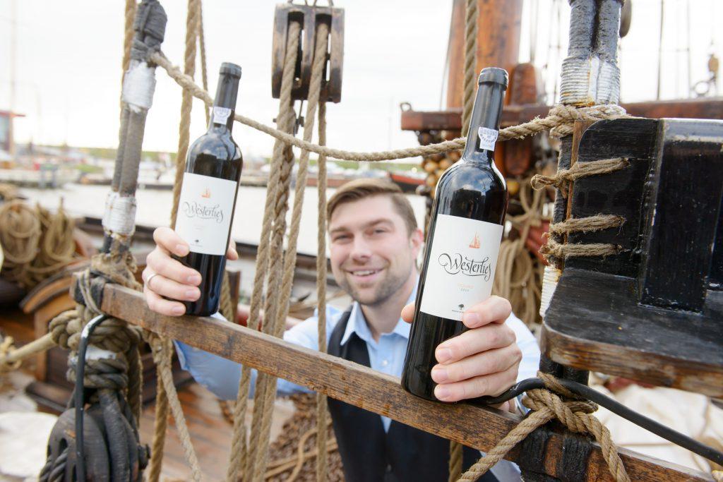Mann hält zwei Flaschen Westerlies BioWein in der Hand