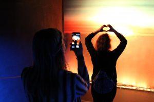 Eine Frau fotografiert eine andere Frau vor einem Sonnenuntergang.