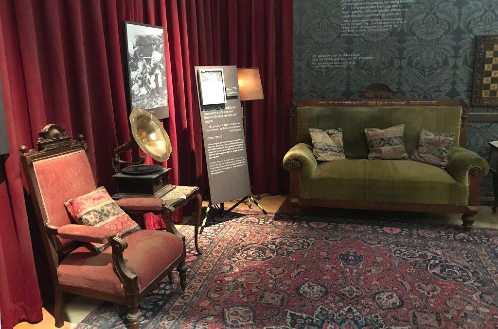Blick in ein altes Wohnzimmer: rotes Sofa, grüner Sessel, Grammophon, dazwischen Ausstellungstafeln