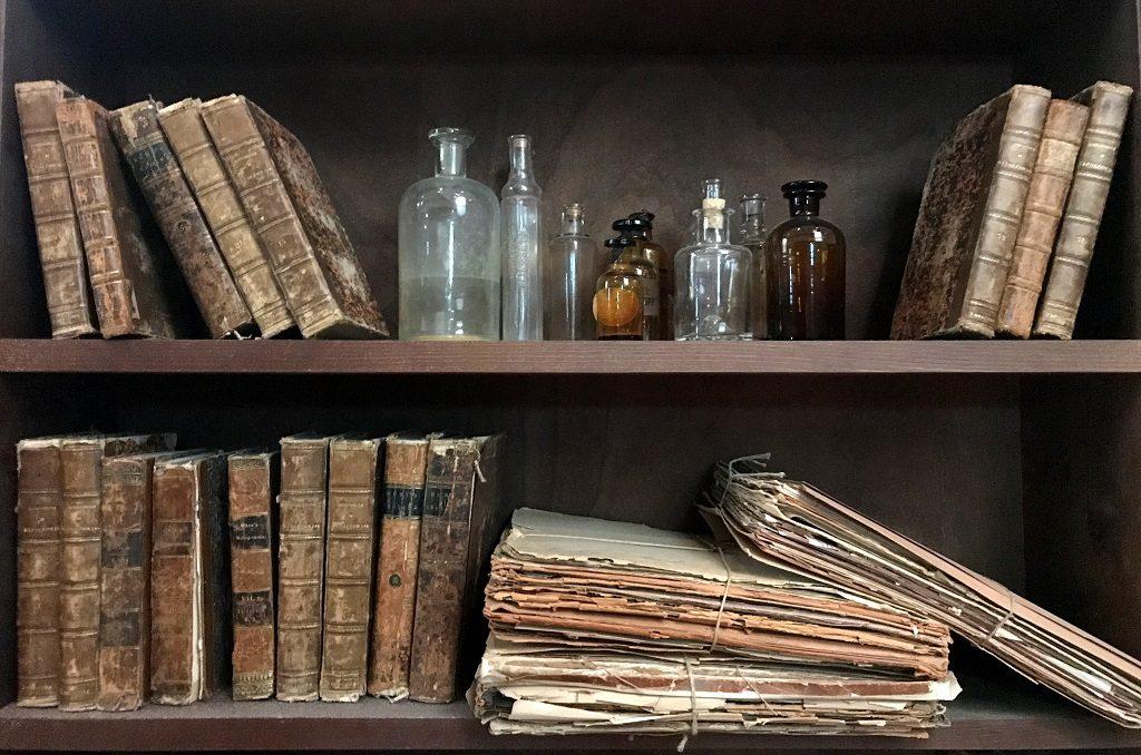 Regal mit alten Büchern und Fläschchen