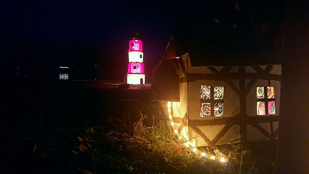 Ein kleines Häuschen mit bunten Fenstern und ein Leuchtturm (c) Annika Jaeger