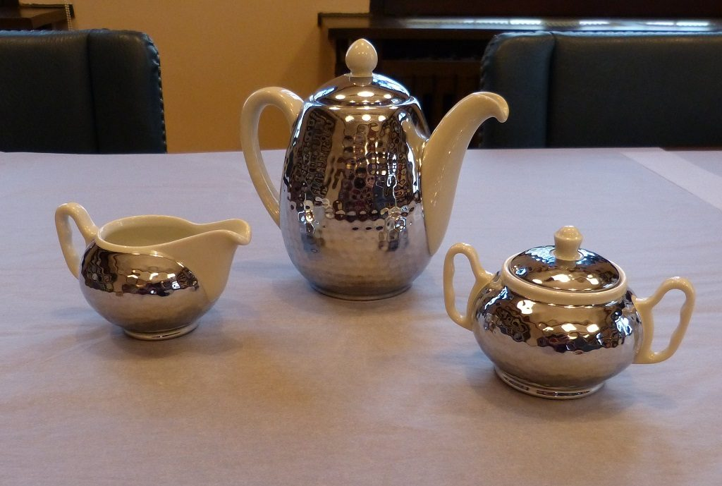 Eine Kaffeekanne mit zwei kleineren Kännchen auf einer weißen Unterlage