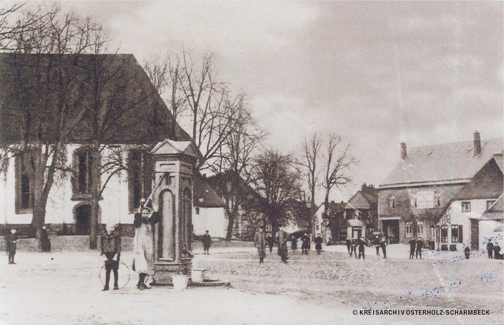 Ein historisches Foto von Scharmbeck: links eine Kirche, in der Mitte ein Marktplatz, rechts mehrere Häuser.