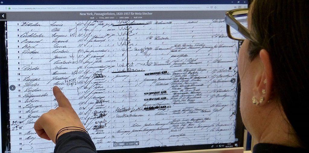 Tanja Fittkau vor einem Ausschnitt aus der Datenbank ancestry.