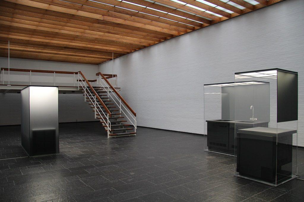 Eine schwarze nachgebaute Küchenzeile, ein Kühlschrank und eine Liege unter einer Glashaube. Im Hauptraum der Kunsthalle Bremerhaven.