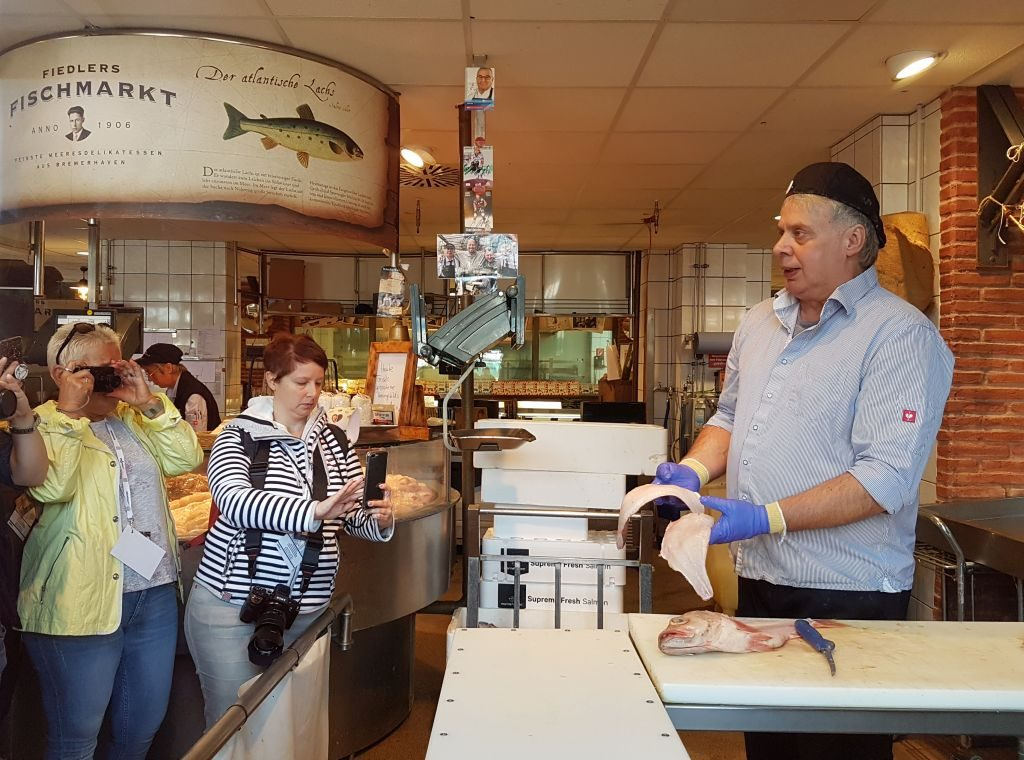André zeigt uns in Fiedlers Fischmarkt anno 1906 das Filetieren von Fisch (c) Tanja Albert