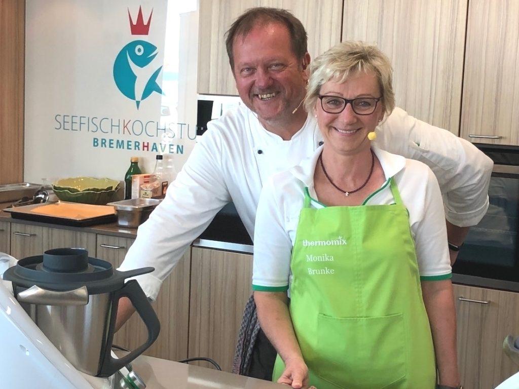Küchenchef Ralf Harms und Thermomix-Repräsentantin Monika Brunke stehen vor Beginn der Kochshow F(r)isch aus dem Thermomix bereit zum Startschuss