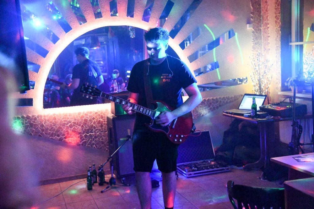 Ein Mann spielt auf einer Gitarre - hinter ihm hängt eine Sonne aus Spiegelglas an der Wand.