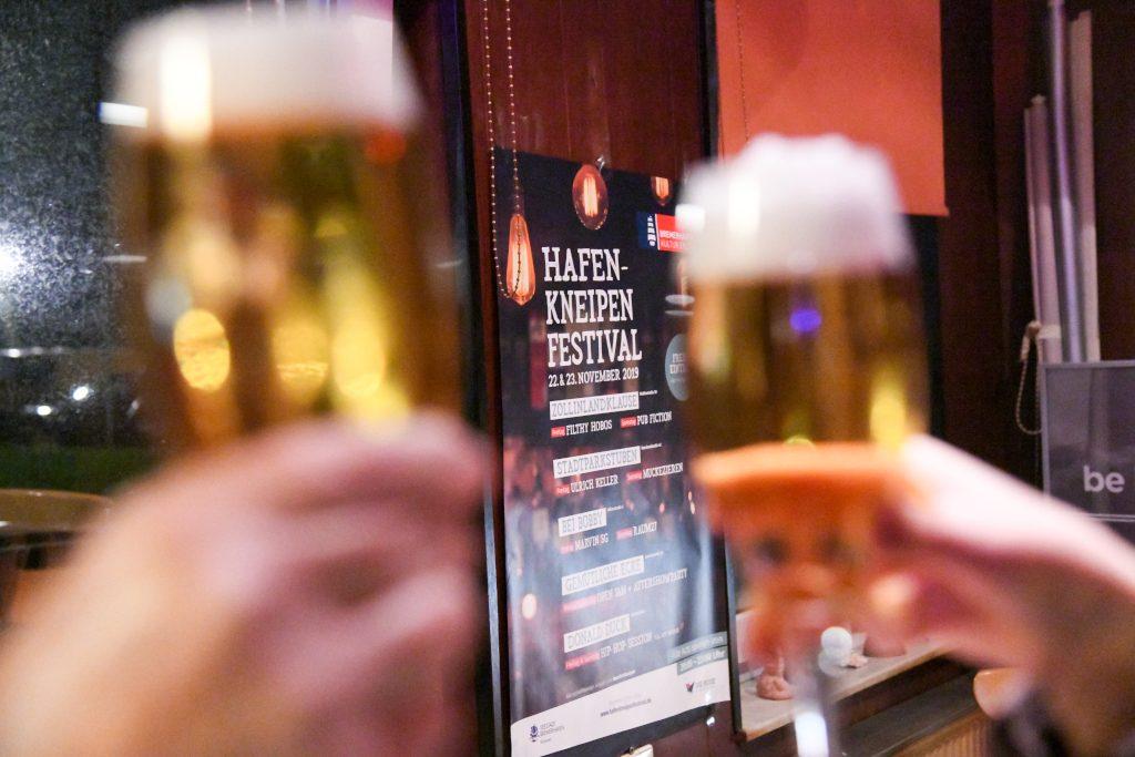 Zwei Personen stoßen mit Bier an. Im Hintergrund hängt das Plakat des Hafenkneipenfestivals