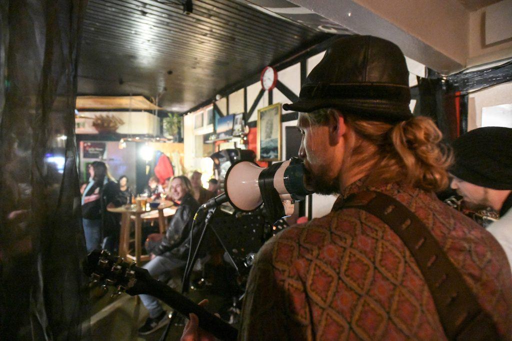 Der Sänger der Filthy Hobos singt beim Hafenkneipenfestival durch ein Megafon in der Zollinlandklause