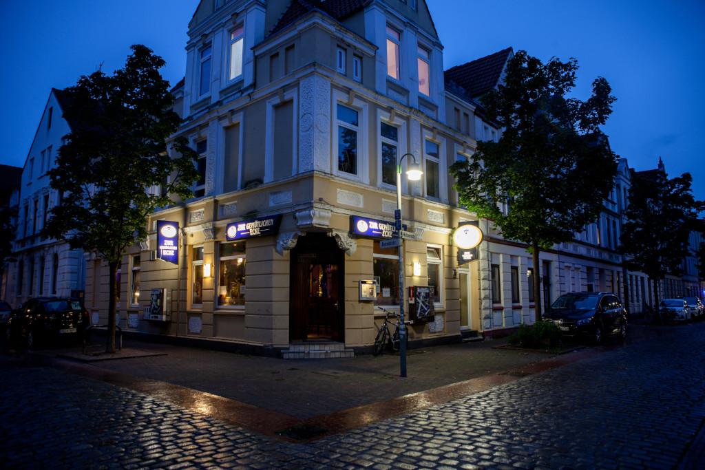 """Eine beleuchtete Hausfassade und der Eingang """"Zur Gemütlichen Ecke"""""""