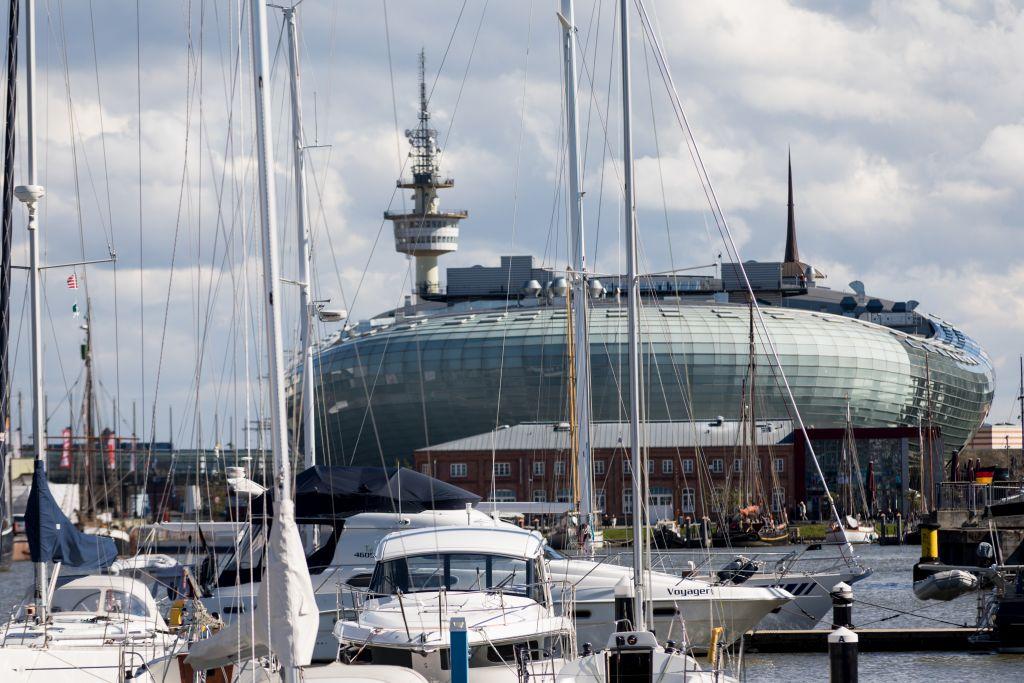Blick vom Neuen Hafen mit Segelbooten darin über das Klimahaus 8° Ost auf den Radarturm