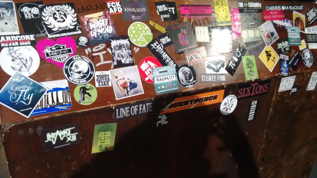 Viele Sticker kleben auf einem Holztresen