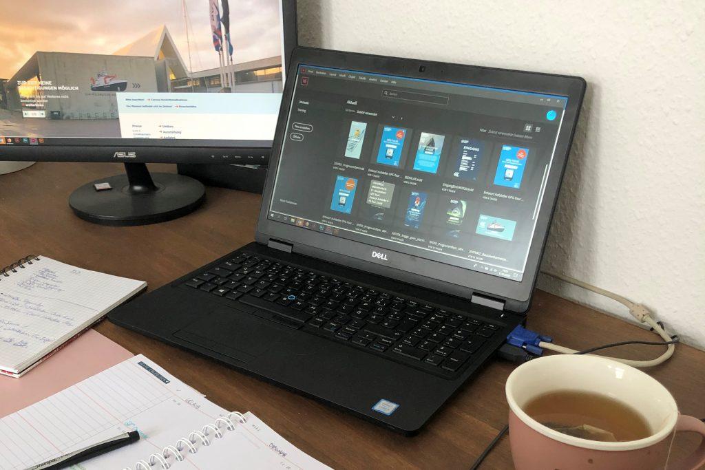 Der Schreibtisch ist für das Homeoffice vorbereitet: Laptop, zweiter Bildschirm, Notizbücher und ein Tee.