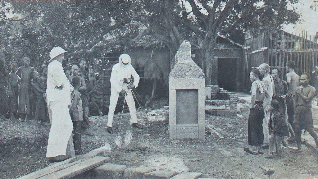 Bild aus dem Erinnerungsalbum des Korvettenkapitäns Hermann Brunswig: ein Fotograf in weißer Kleidung fotografiert eine Gruppe Einheimische.