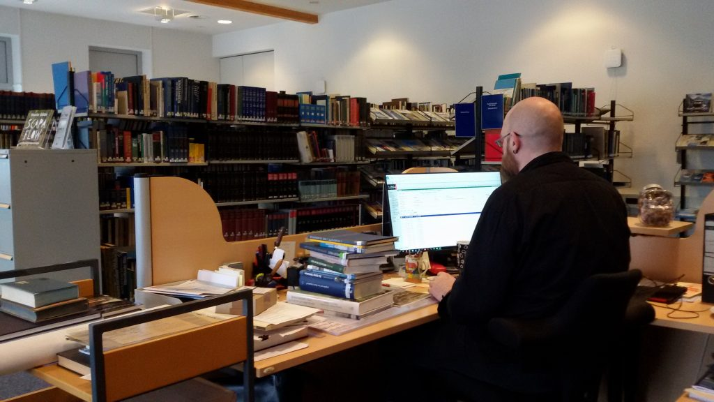 In der Bibliothek sitzt ein Mitarbeiter am Rechner, vor ihm ein Stapel Bücher.