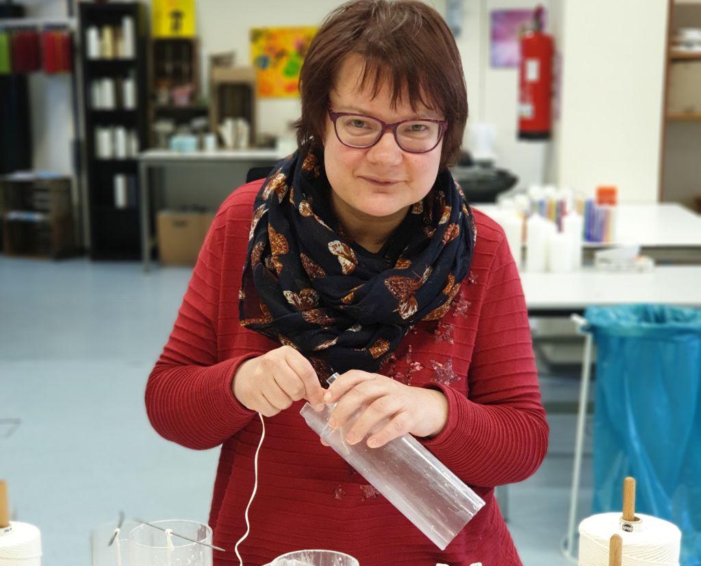 Anika Riggers fädelt einen Docht in die Kerzenform (c) Archiv EWW