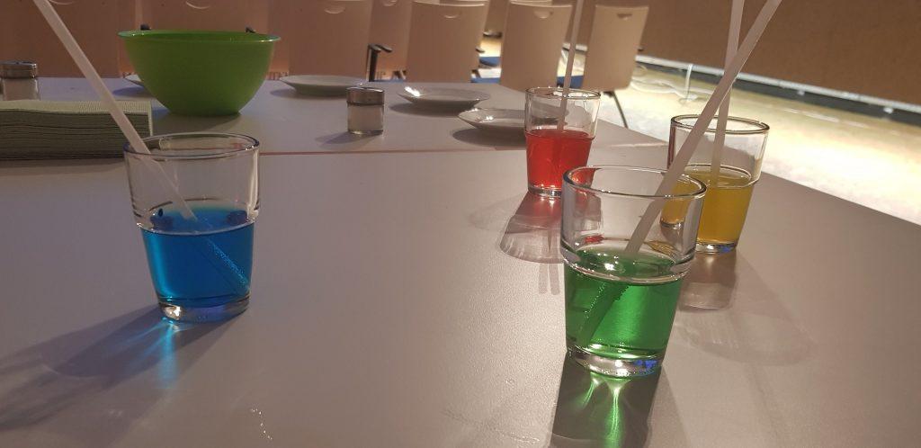 Blaue, rote, gelbe und grüne Flüssigkeit in Gläsern steht für ein Experiment bereit.