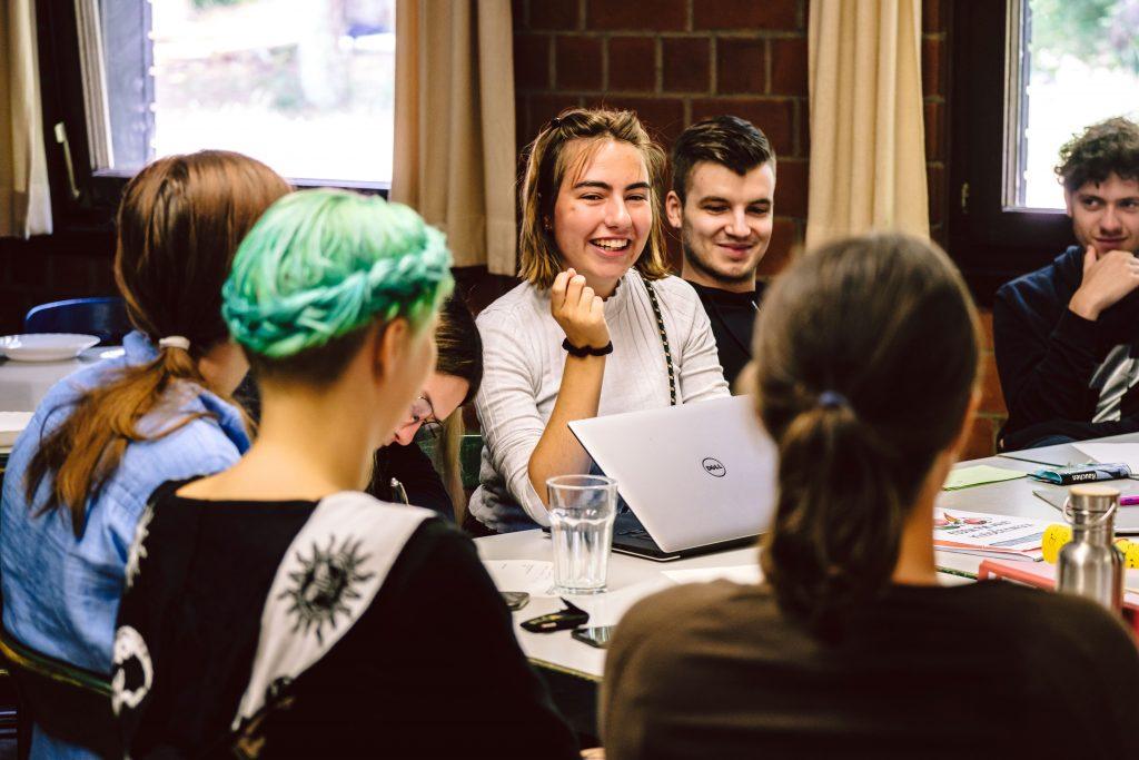 Eine Gruppe Jugendlicher sitzt beisammen und arbeitet in einem Workshop im Rahmen eines FSJ-Seminarwochenendes