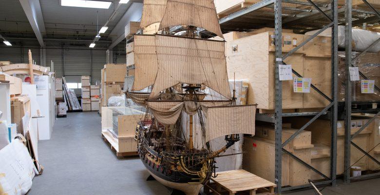 Schiffsmodelle lagern in selbstgebauten Kisten in Hochregalen. Einige Modelle sind so groß, dass sie nicht in Kisten passen.