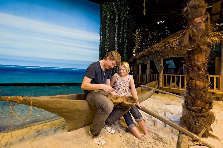 Ein junger Mann und ein Mädchen sitzen auf einem Holzboot am Strand und haben eine Kokosnussschale in der Hand (c) Jan Rathke