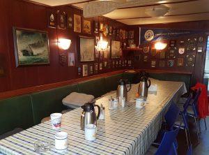 """Tisch mit Sitzecke und Plaketten an der Wand an Bord der """"Wal"""" (c) Tanja Albert"""