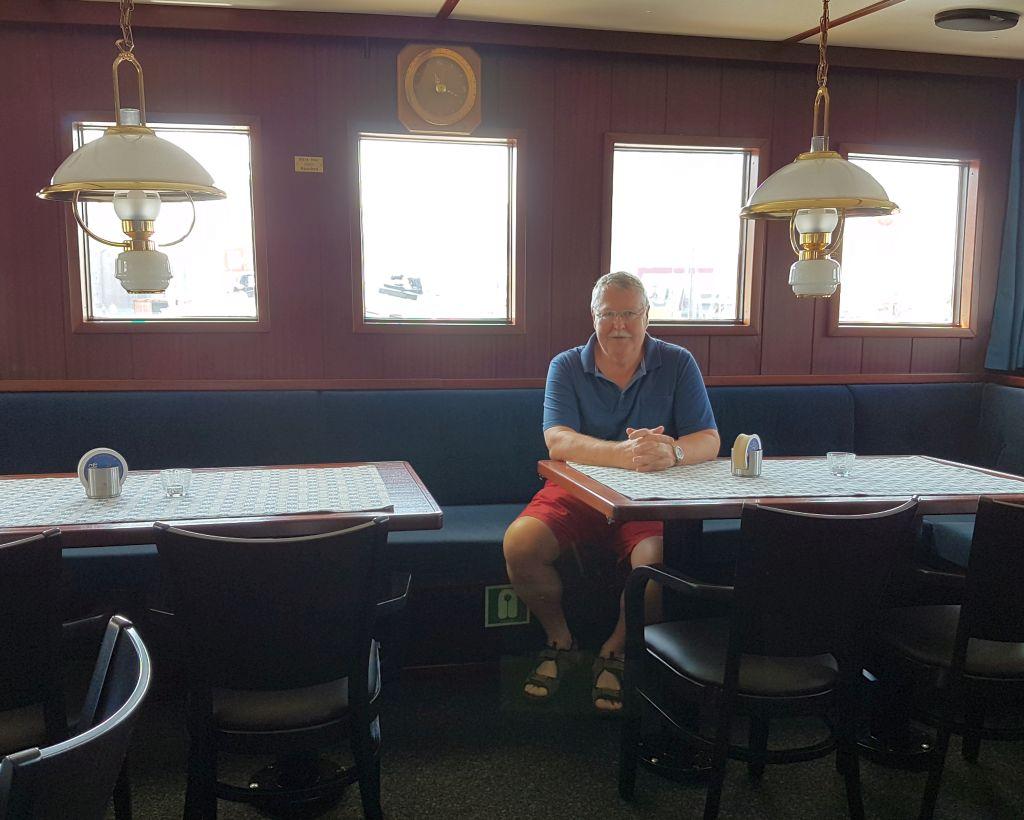 """Ingo Daul sitzt am Tisch im Salon auf der """"Wal"""" (c) Tanja Albert"""