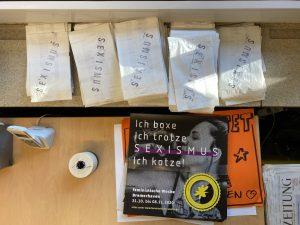 """Flyer und Plakate der Feministischen Woche mit dem Aufdruck """"Ich boxe, ich trotze, sexismus ich kotze"""""""