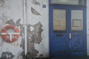 Schäbige, blaue Eingangstür mit Fassade, an der die Farbe abblättert (c) Tanja Albert