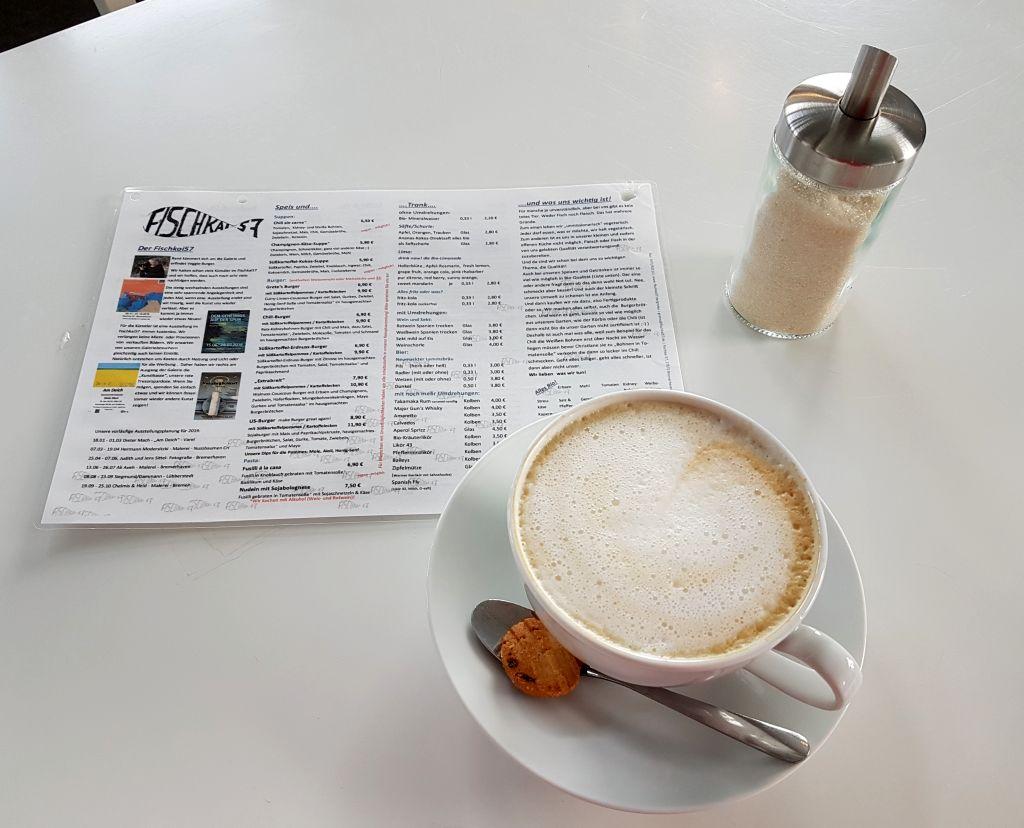 Milchkafee mit Zuckerstreuer und Speisenkarte auf dem Tisch (c) Tanja Albert