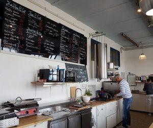 Offene Küche mit Tafel, auf der Speisen angeschrieben stehen im Grete's (c) Tanja Albert