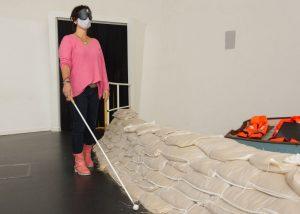 Blind: Tanja mit Mund- und Nasenschutzmaske sowie Augenmaske und Langstock in einem Raum in Klimahaus 8° Ost (c) Andreas Larmann