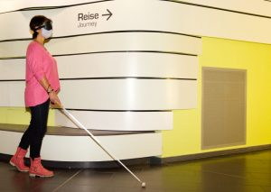 Tanja ertastet sich mit Hilfe eines Langstocks und mit einer Augenmaste versehen den Weg durchs Klimahaus 8° Ost (c) Andreas Larmann