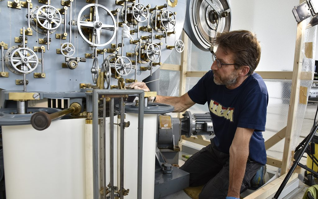 Restaurator Tim Lücke vor dem Gezeitenrechner zu Beginn der Restaurierung.
