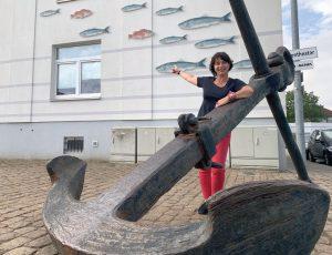 Tanja hinter einem Stockanker und vor einer Hausmauer mit Fischmotiven (c) Lina Selimi