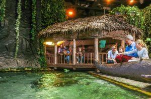 Menschen unter einem Palmdach vor einem Wasserbecken im Klimahaus Bremerhaven 8° Ost (c) hv Schwarze Klimahaus