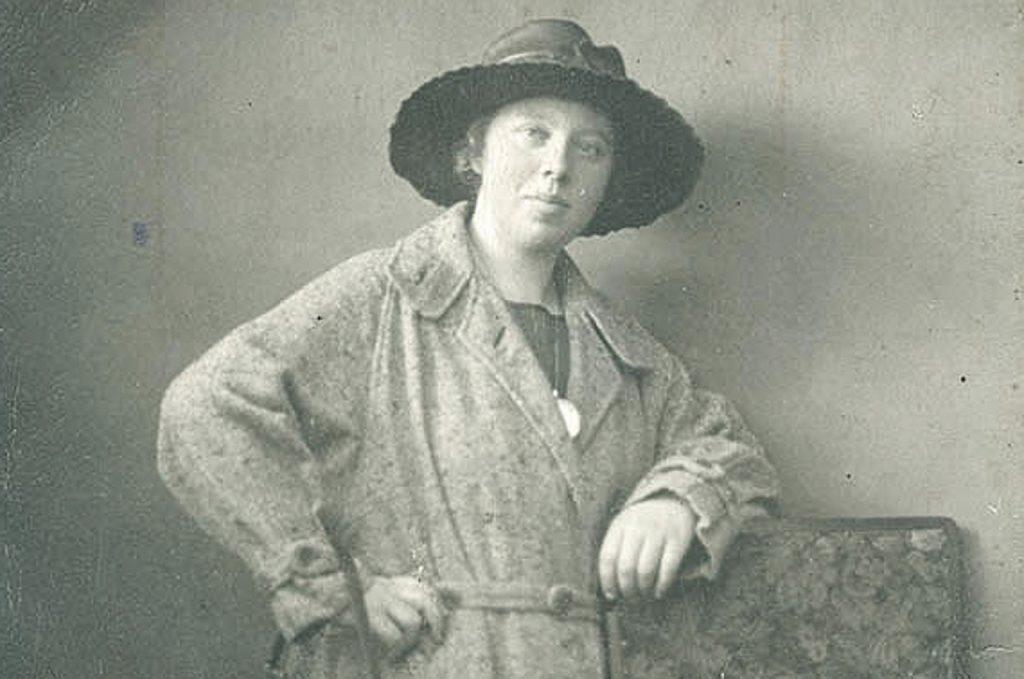 Studioaufnahme einer jungen Frau mit Hut. Selbstbewusst lehnt sie den Arm auf einen Stuhl.
