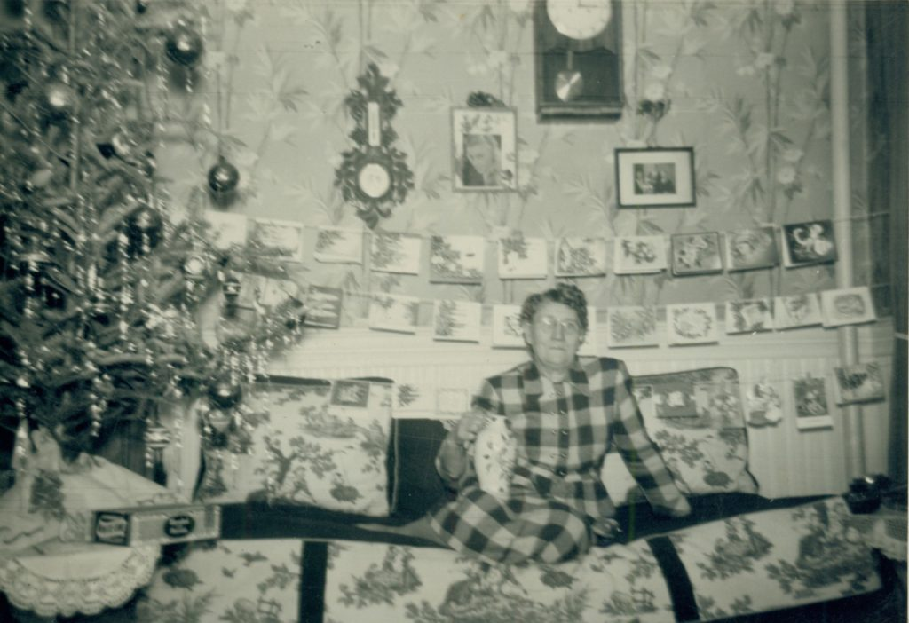 Eine ältere Dame im Karokleid mit Brille. Ihre Beine liegen auf der Couch, neben ihr steht ein Weihnachtsbaum. Sie lächelt.