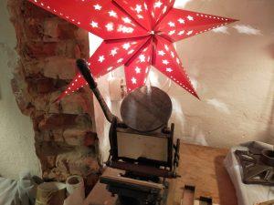 Ein roter Weihnachtsstern hängt über einer Handdruckpresse