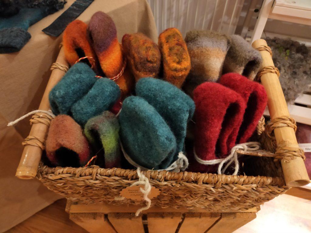 Sieben Paar Hausschuhe aus Filz stecken in einem Korb