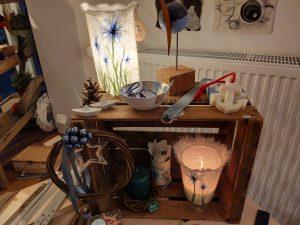 auf und in einer Holzkiste stehen verschiedene Kunsthandwerkprodukte