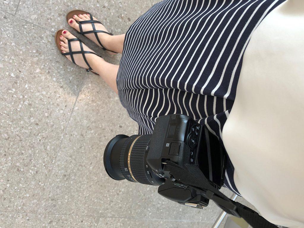 Ein typisches Arbeitsoutfit im Sommer: Sandalen, Rock und immer dabei: die Kamera.