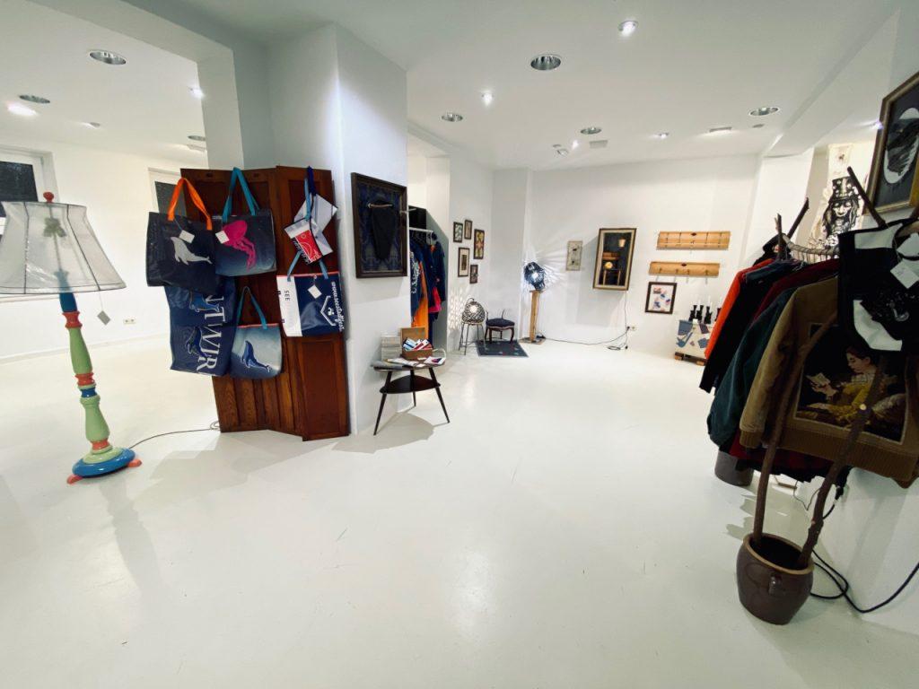 Wir sehen Kleidung und Möbel ausgestellt in einem Raum