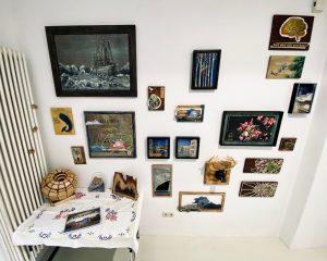 Bilder hängen an einer Wand. Sie zeigen unterschiedliche Motive