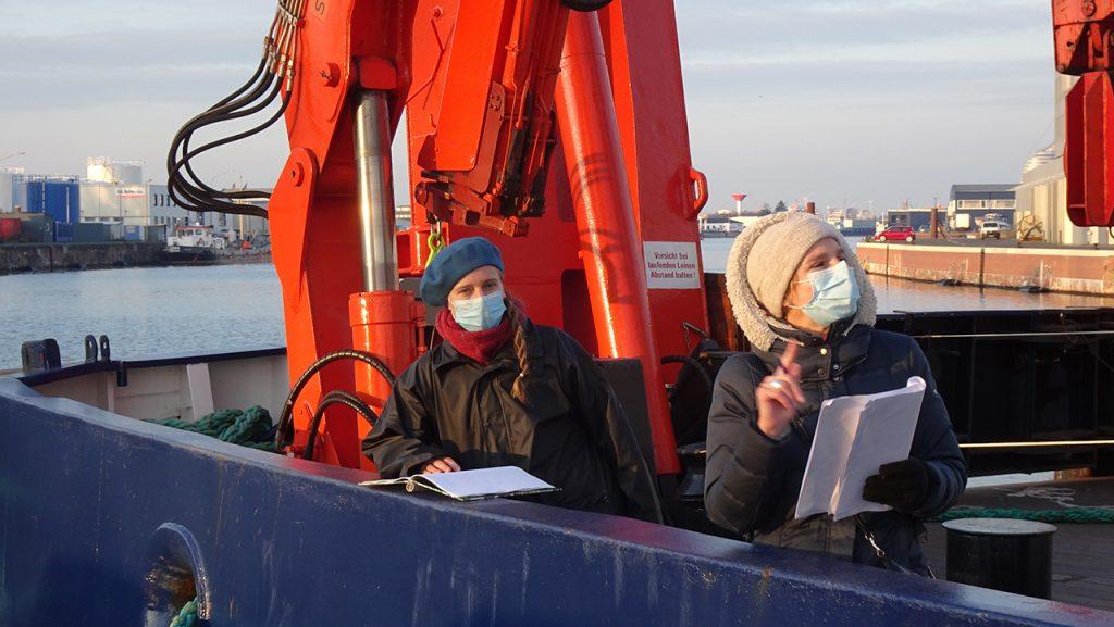 Auch an Deck der HEINCKE wurden Aufnahmen gemacht: mit Script in der Hand und Mund-Nasen-Bedeckung im Gesicht.