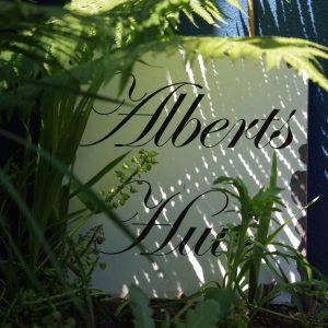 """ein Schild auf dem in verschnörkerter Schrift """"Alberts Huus"""" steht."""