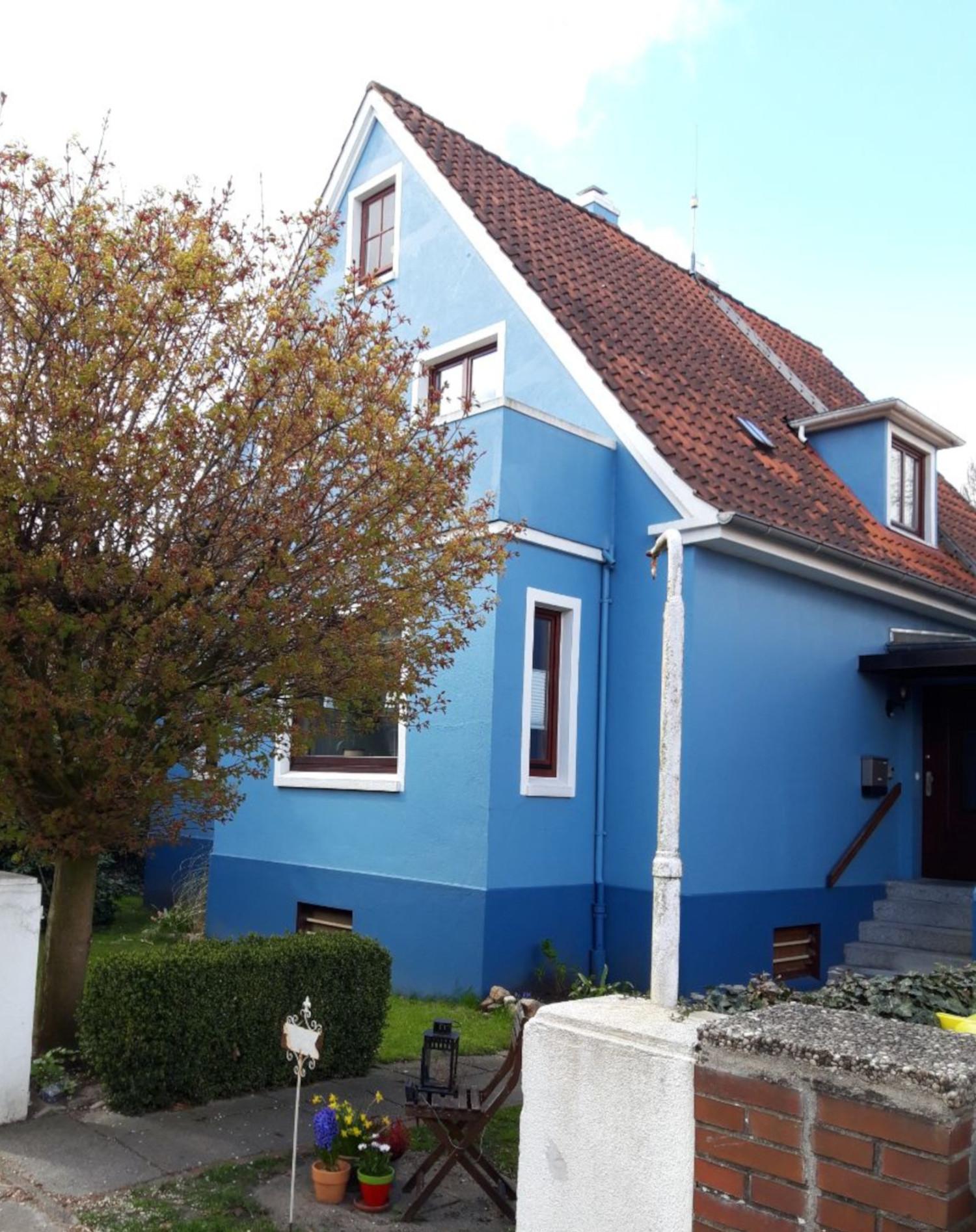 ein blaues Häuschen mit weißen Fensterrahmen