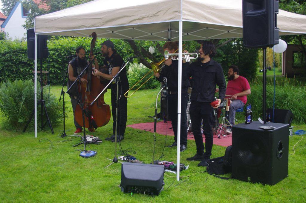 Unter einem Pavillon spielt die Band Carry Nation & the Speakeasy Kontrabass, Gitarre, Posaune; Trompete und Schlagzeug