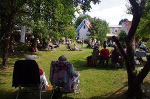 Im großen Garten sitzen mehrere Personen auf Bänken, Campingstühlen, Liegen... und genießen die Sonne